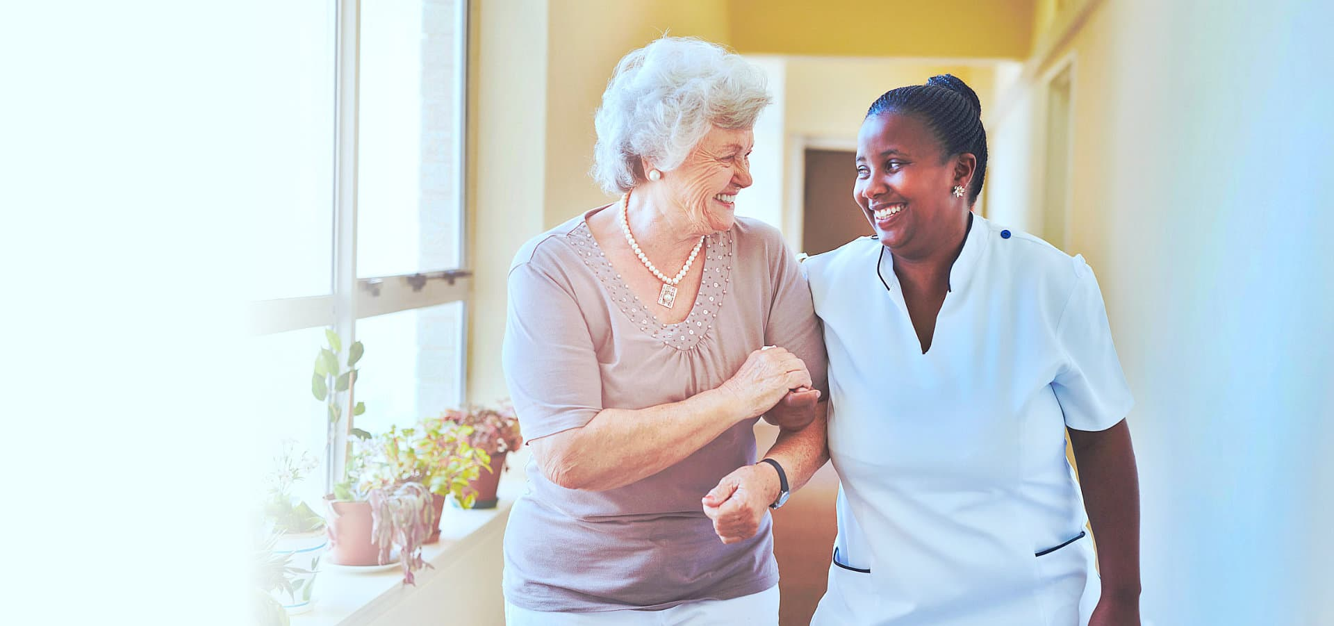 happy elderly woman assisted by her caregiver
