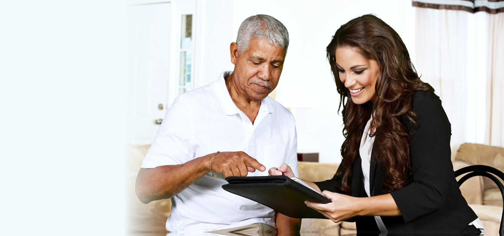 elderly man with a woman filling up a form