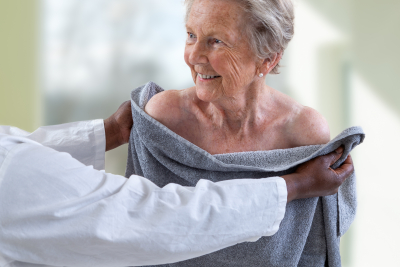 caregiver assisting senior woman for shower and drying her