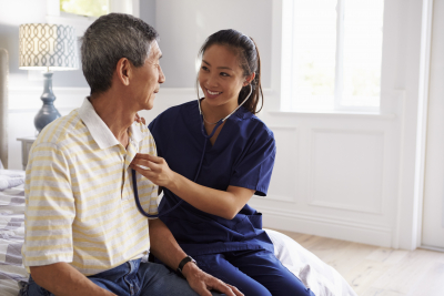 nurse making home visit to senior man for medical exam