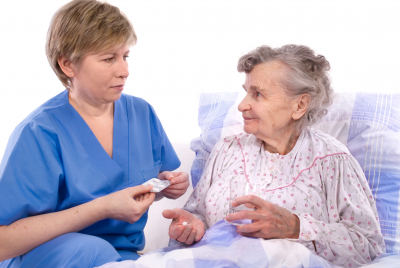 caregiver reminding to the senior woman take a medicine